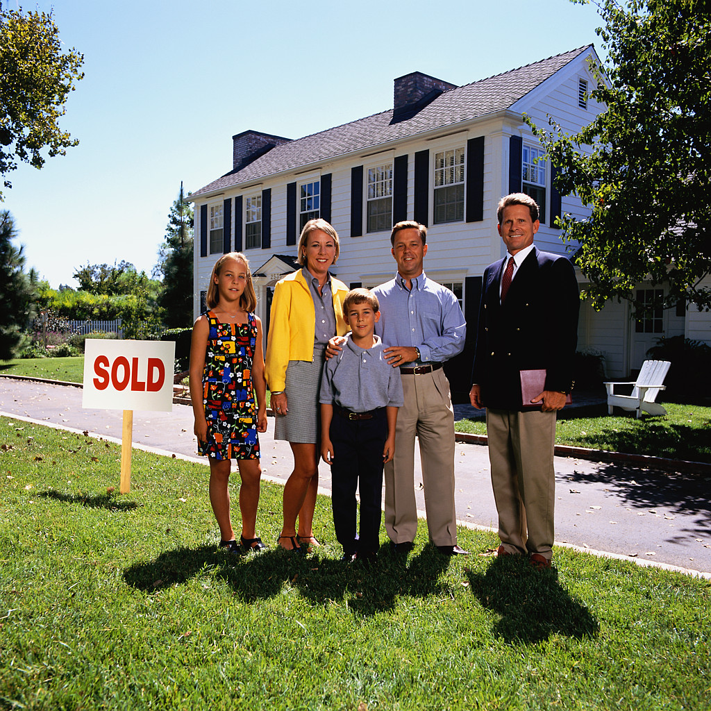 family standing with agent in front of a house with a sold sign