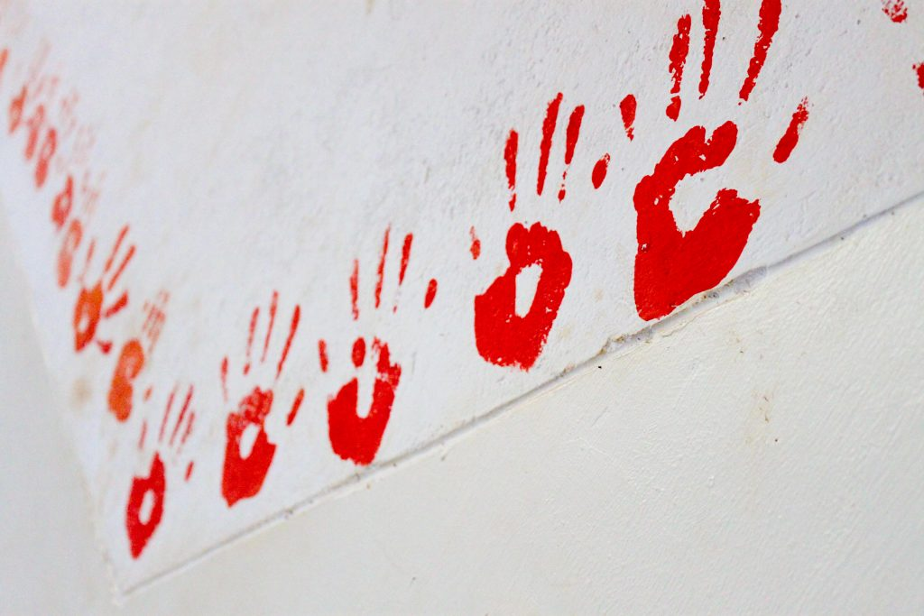 little red hands stamped on a white wall