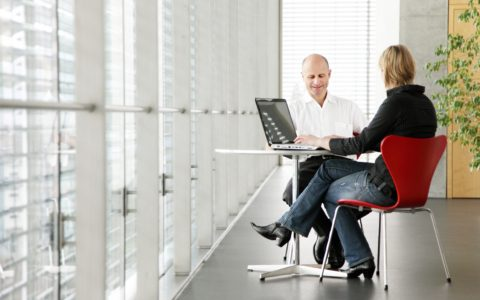 one-on-one business meeting at small table with laptop