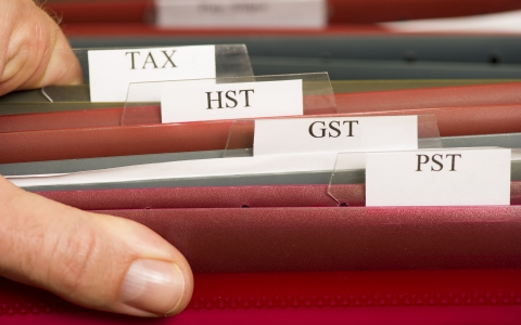 File folders that are labelled GST, HST, PST and Tax