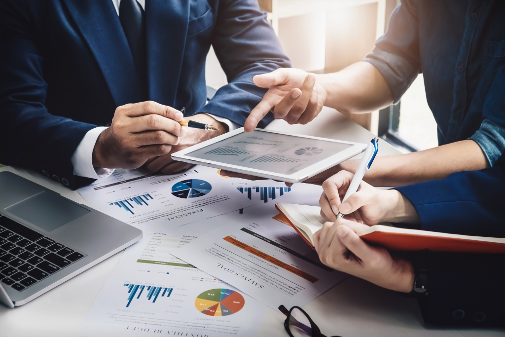 Business people in a meeting with graphs and financial data on table in discussion