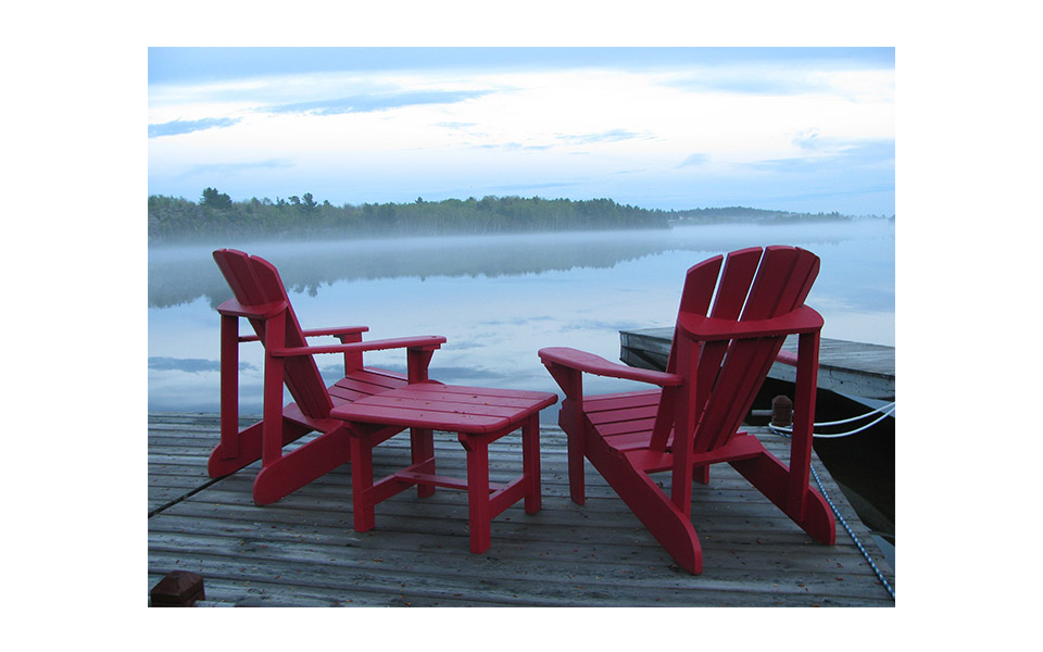 Cottage life -a dock on the water with 2 red Adirondack chairs