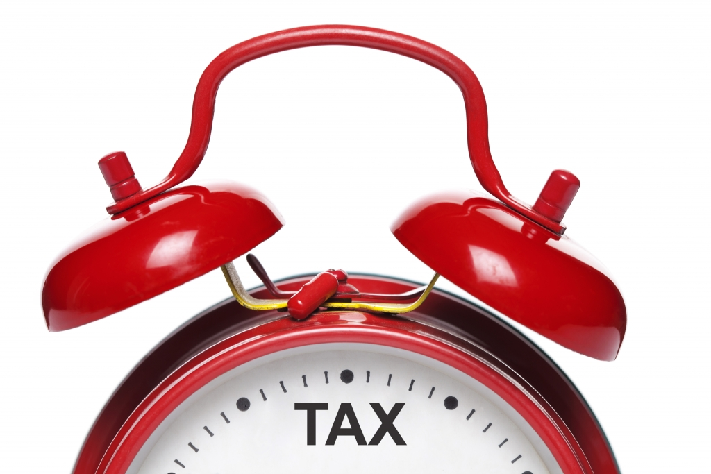 Red alarm clock with tax written at 12 position