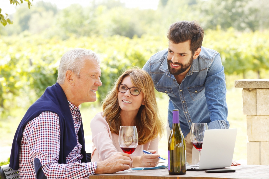 Elderly man sitting with younger middle age children in vineyard