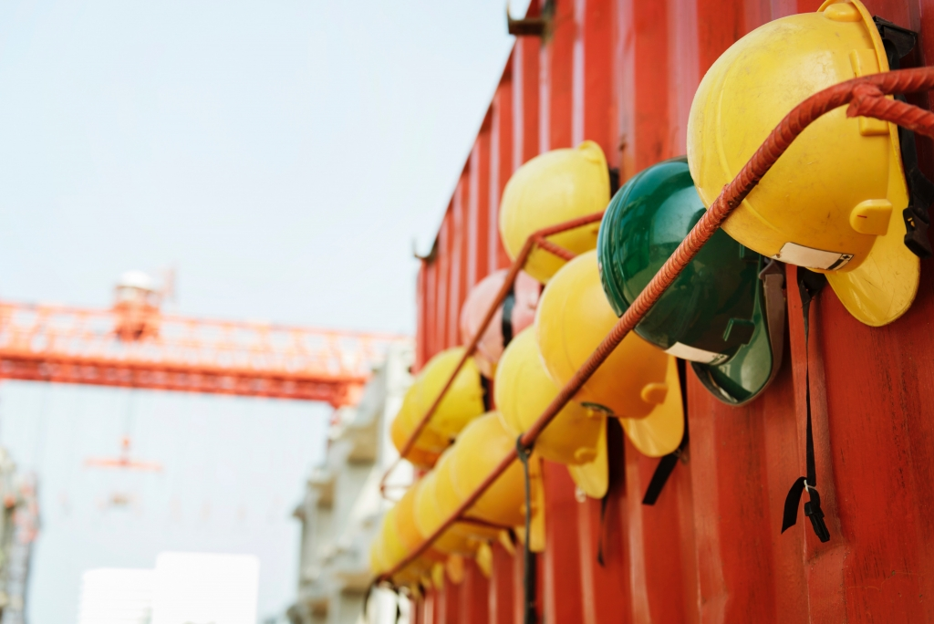 hard hats hung on a wall at the construction site