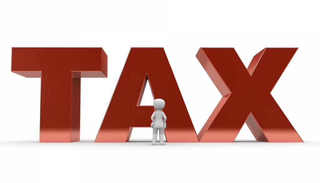 The word tax (large) with a little computer generated person looking up at it