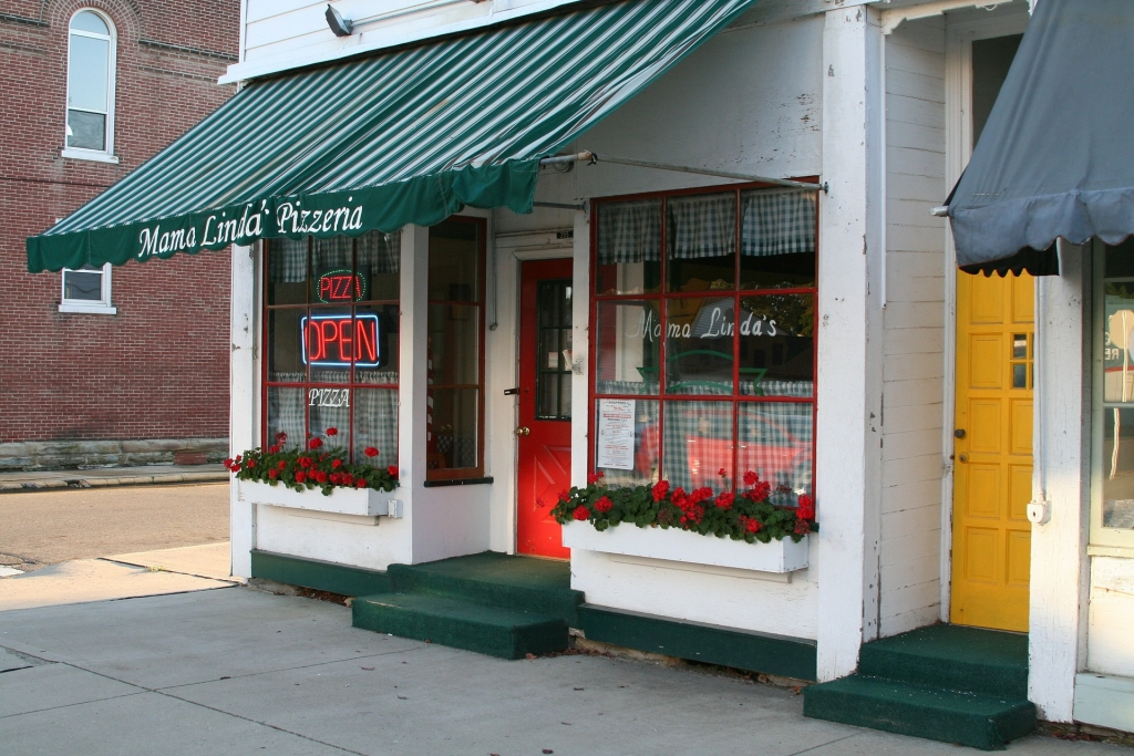Front of White Building with Red Door and Green Roof. Open sign in window.