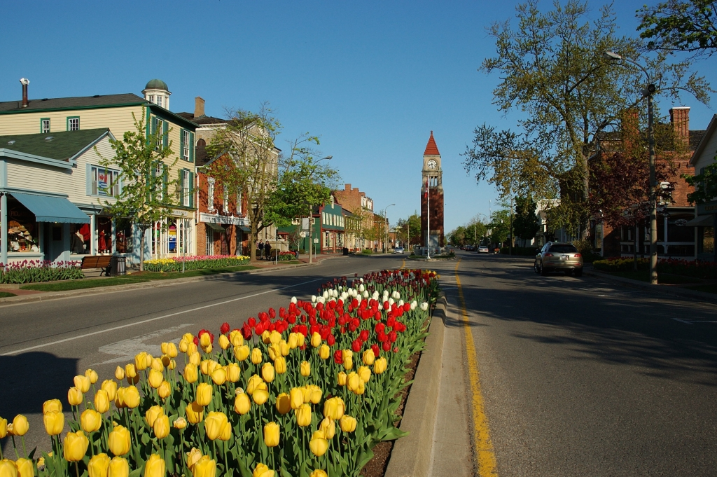 A view looking west along Queen Street, Niagara on the Lake, Ontario, Canada showing the profusion of spring flowers, with the Clock Tower.