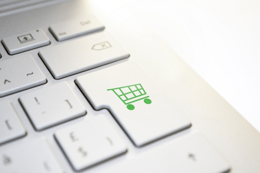 computer keyboard with a shopping cart button in green