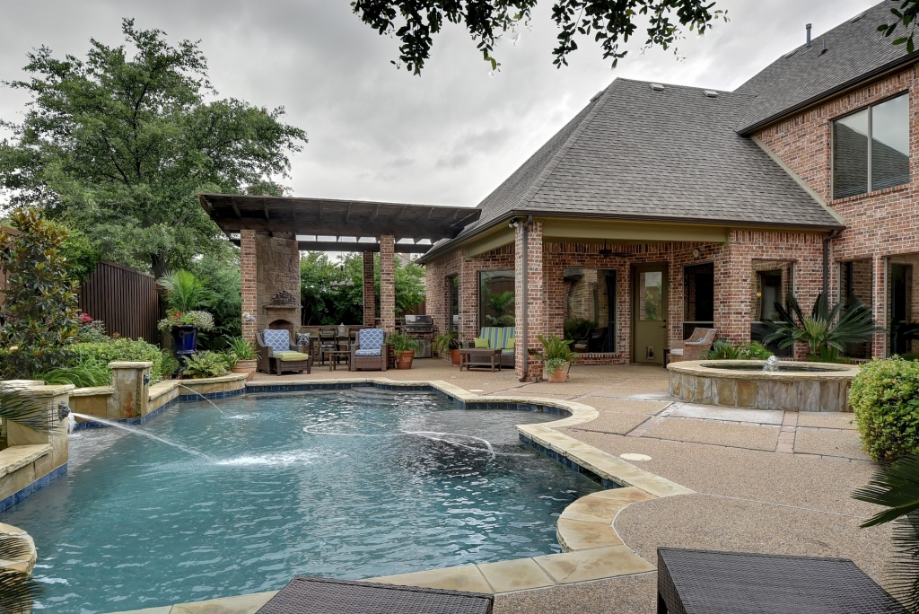 Inground pool in backyard with patio furniture and landscape