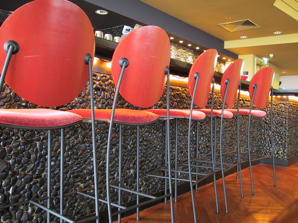red bar chairs in front of a gray stone bar