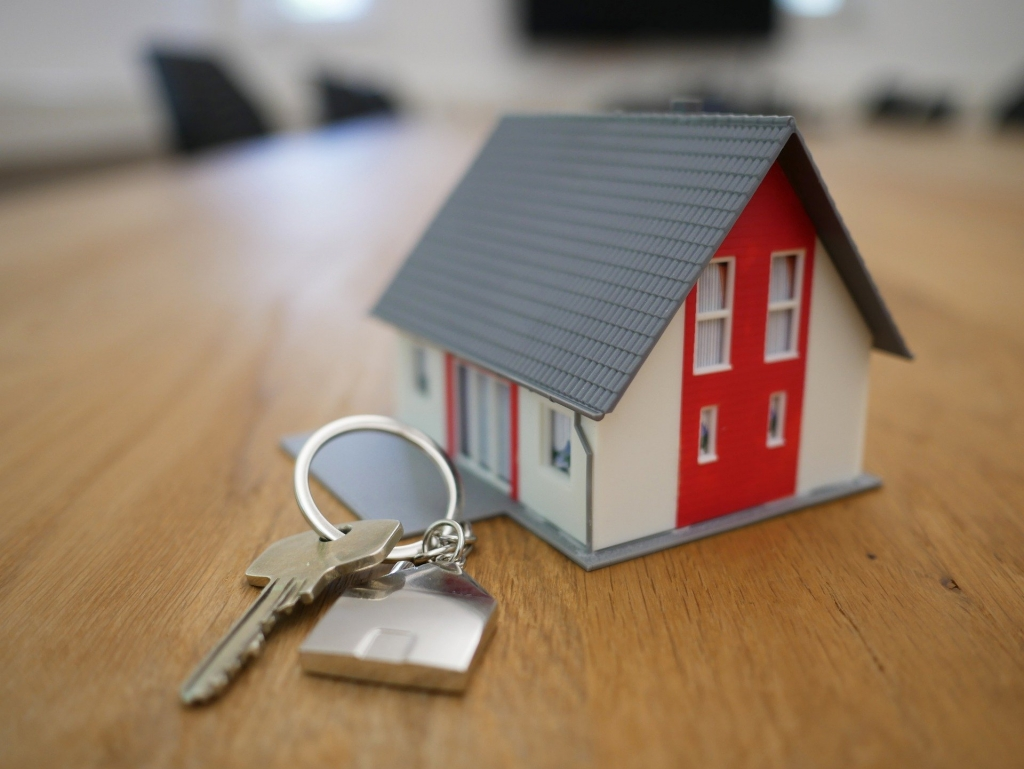 Little toy house with keys on wood table