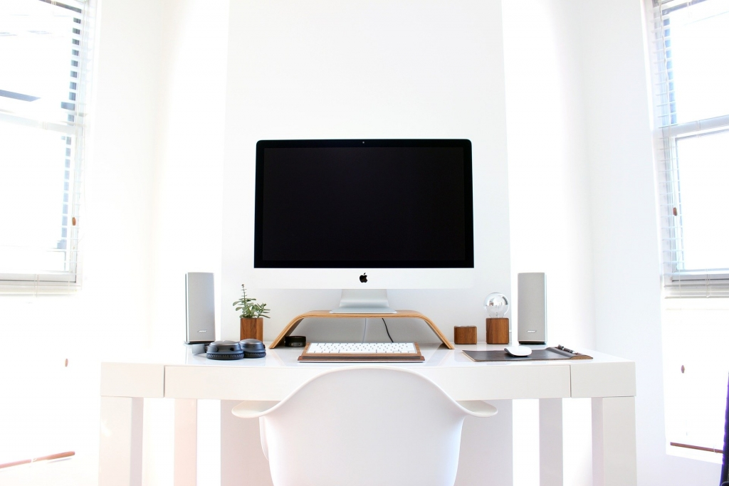 computer sitting on a white desk in a white room