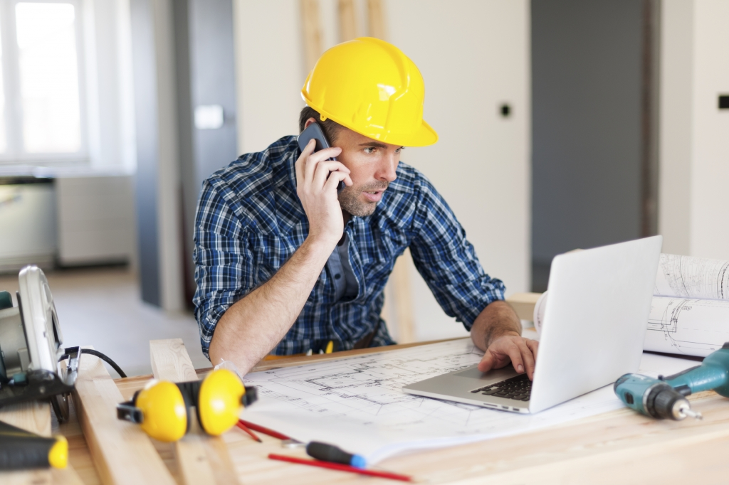 construction worker looking at laptop and sitting at his desk with his phone
