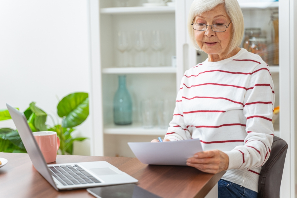 Elderly women sitting by a computer filling out paper work in her kitchen
