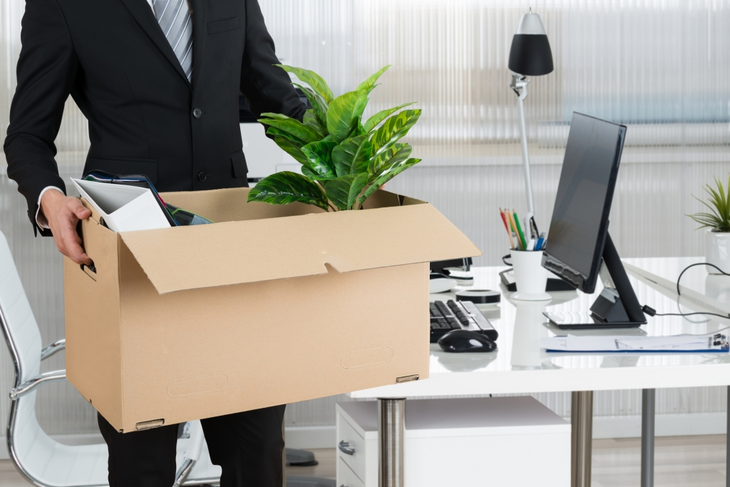 Midsection of businessman carrying cardboard box by desk in office