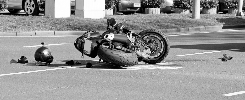 motorcycle laying on pavement. Photo black and white.