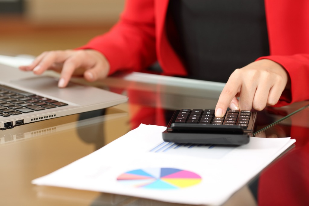 Businesswoman wearing red jacket on calculator and laptop with pie chart on table