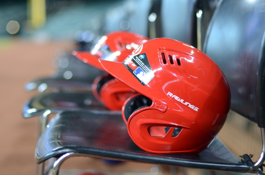 Red baseball helmets in a row on chairs