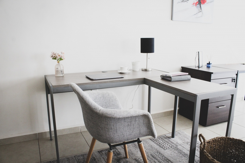 white corner desk and white chair. Laptop on desk.