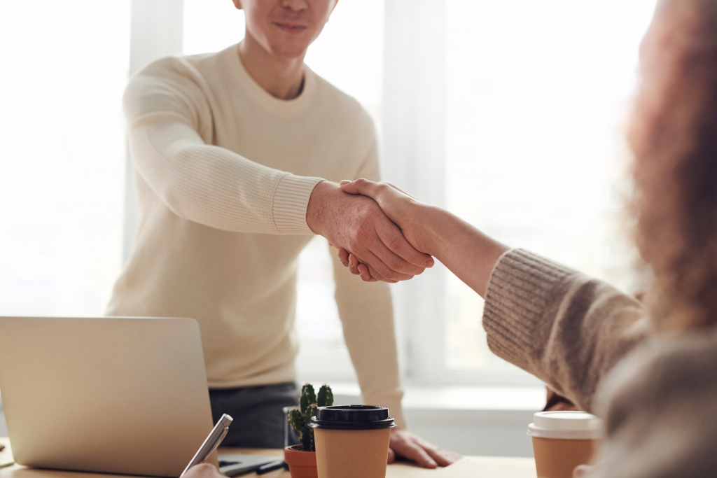 close-up of two people shaking hands at a desk