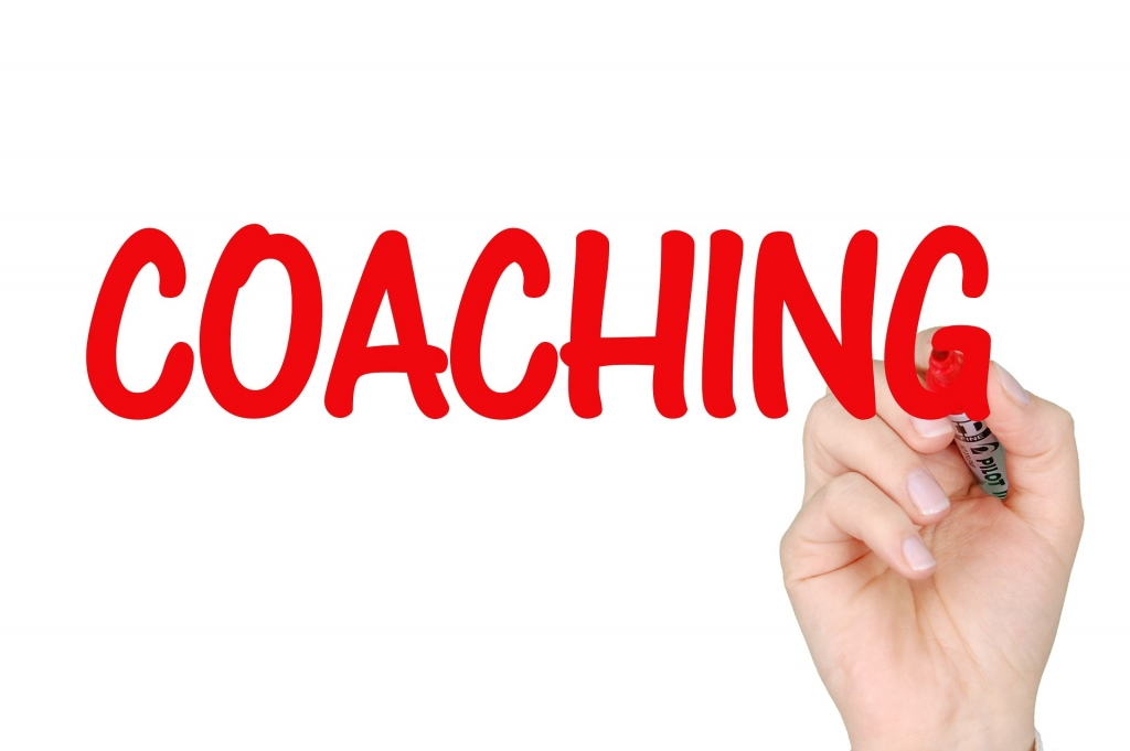 the word coaching is written in red marketing with a hand
