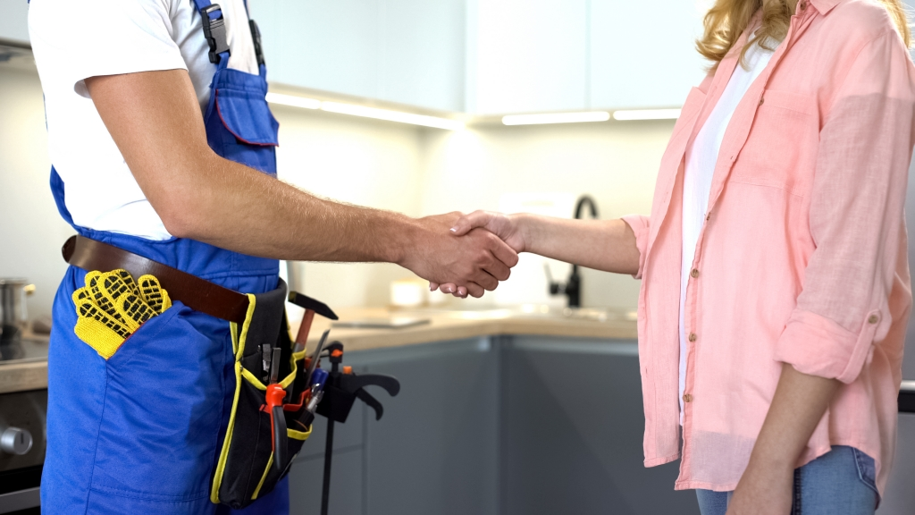Plumber with tools shaking client hand, technical maintenance, repair services