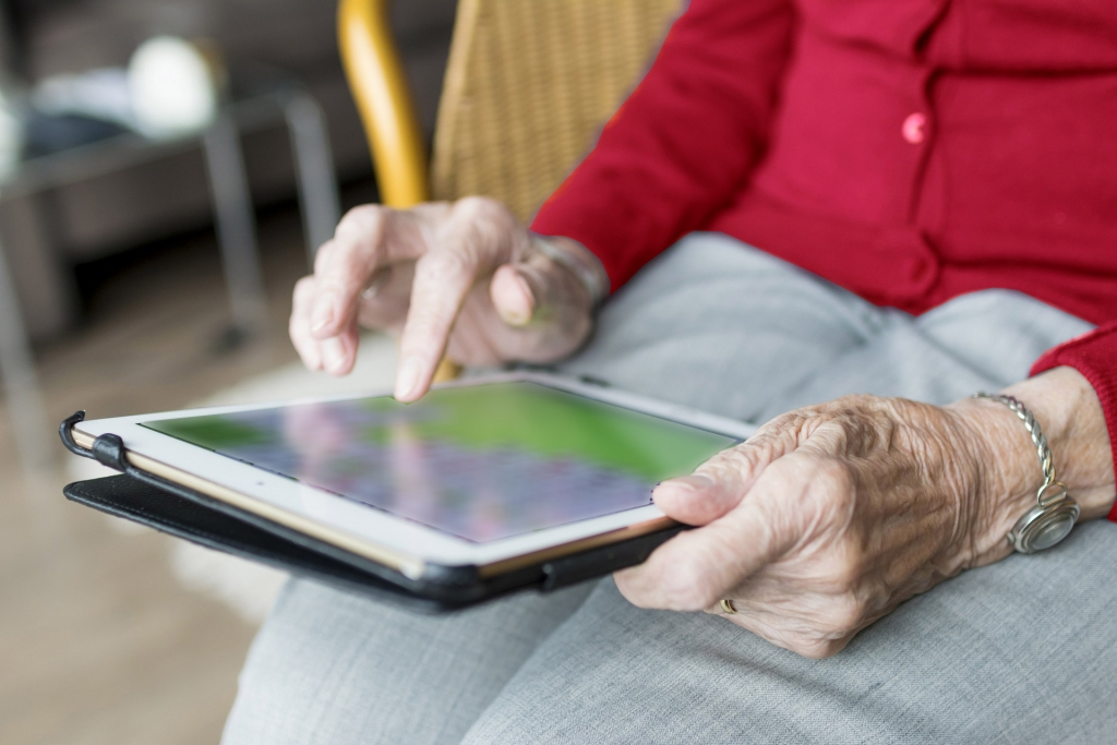 close up of an elderly person holding a laptop