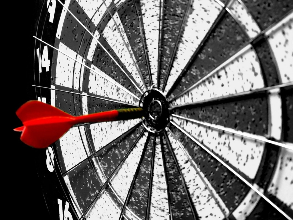 black and white dartboard with red dart in bullseye