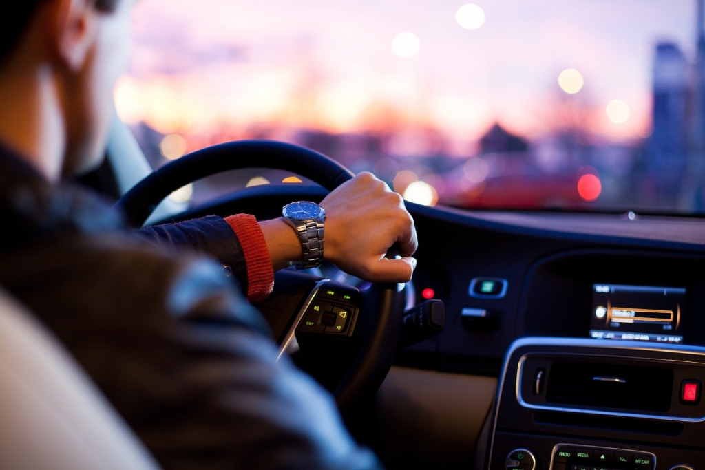 close up of persons hand, holding a steering wheel