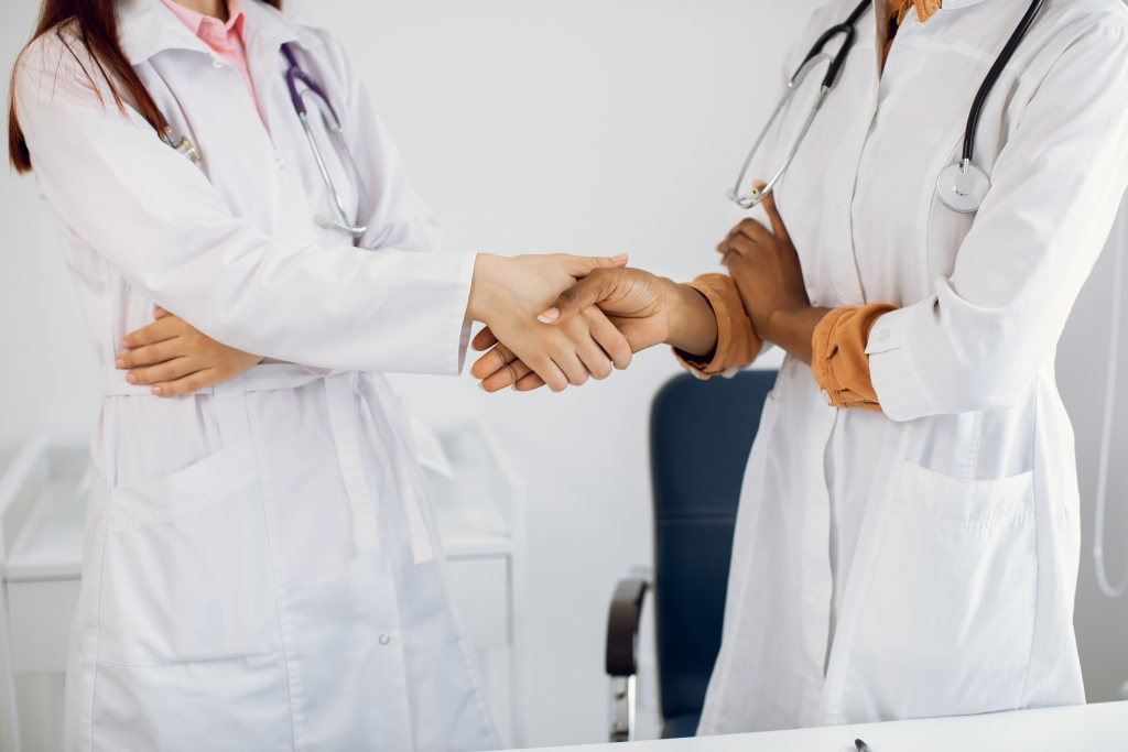 Healthcare, agreement and hiring concept. Two unrecognizable professional multiracial diverse female doctors handshaking at modern hospital, hands close up