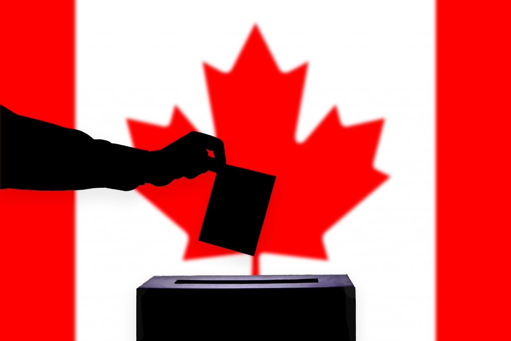 close-up of hand putting a ballot in a box, Canadian flag behind